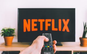 Photo of a hand with a remote pointing at a TV with Netflix playing
