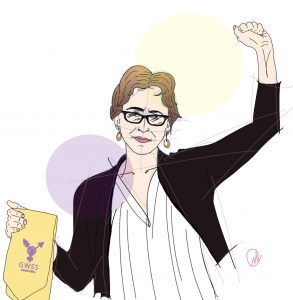 Author Julie Shayne, holding a GWSS sash with a transfeminism symbol on it in her right hand, and her left fist in the air