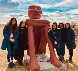 Five women pose by statue at Standing Rock Lakota Sioux Reservation