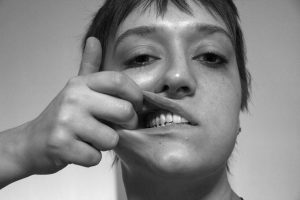 Stifle, art by Lauren Raimunde, shows a young person with two fingers holding their mouth open