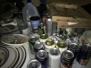 Tabletop covered with takeout garbage, beer cans, and old milk jug.