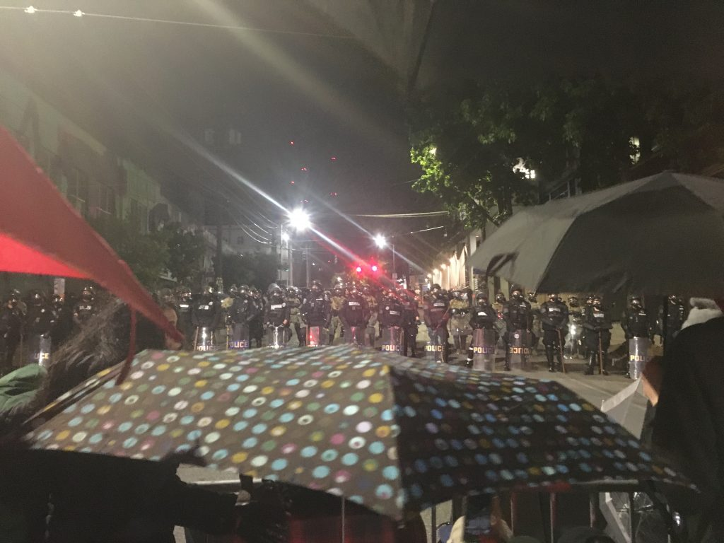 Protestors facing line of armed riot police