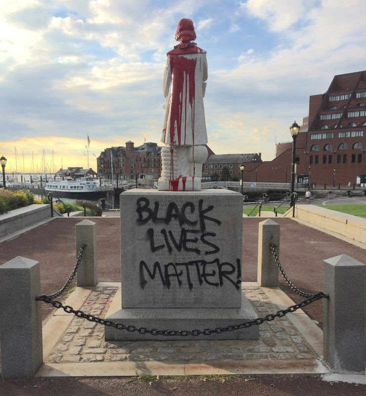 Black Lives Matter and red paint on defaced statue of Christopher Columbus in Boston's North End waterfront park.