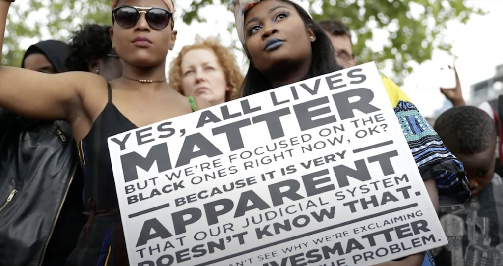 """Two women hold a placard with the slogan """"Yes, all lives matter"""" as people gather in Brixton, south London to protest against police brutality in the US, on July 9, 2016, after two recent incidents where black men have been shot and killed by police officers."""