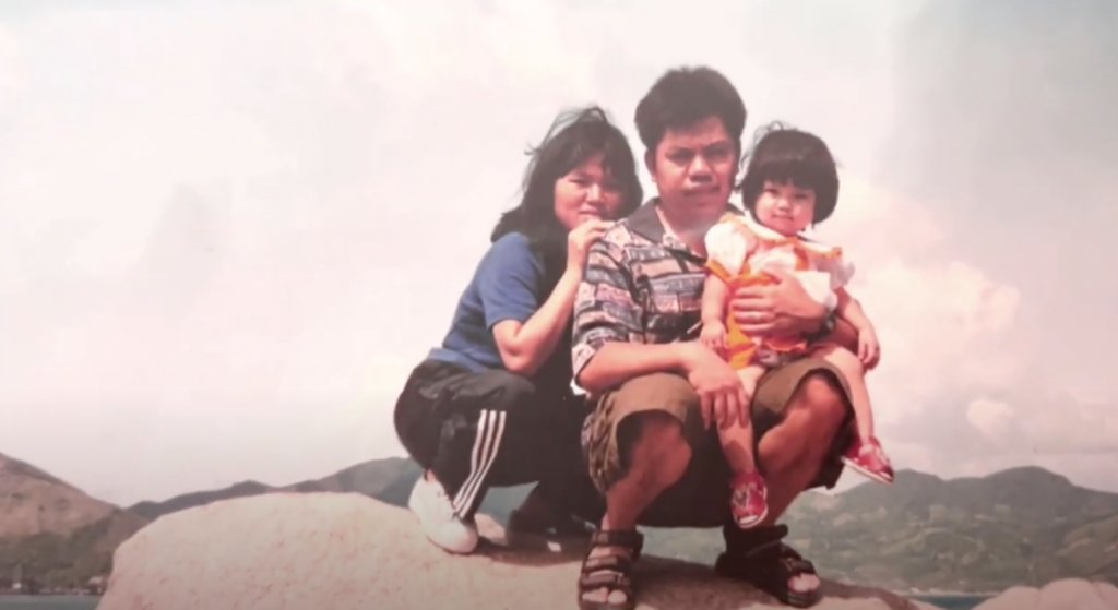 Image of mother, father, and young child crouched on a rock, posing for picture