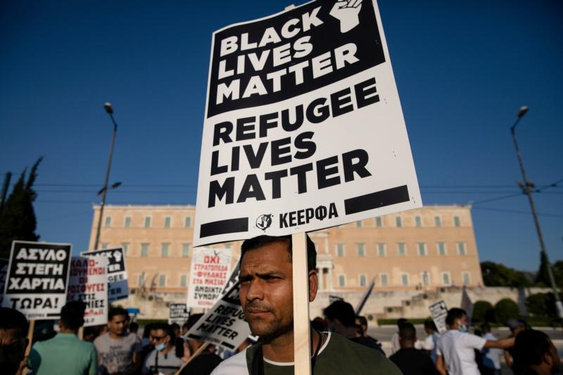 "A man holds a placard reading ""Black Lives Matter, Refugee Lives Matter"" during a demonstration outside the Greek parliament in Athens June 26, 2020."