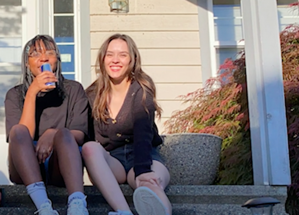 Photo of two people sitting on steps of an entrance to a home