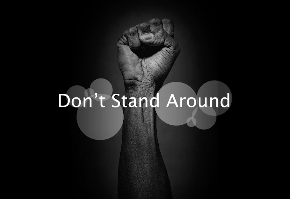 """Image of fist behind words readings """"Don't Stand Around"""""""